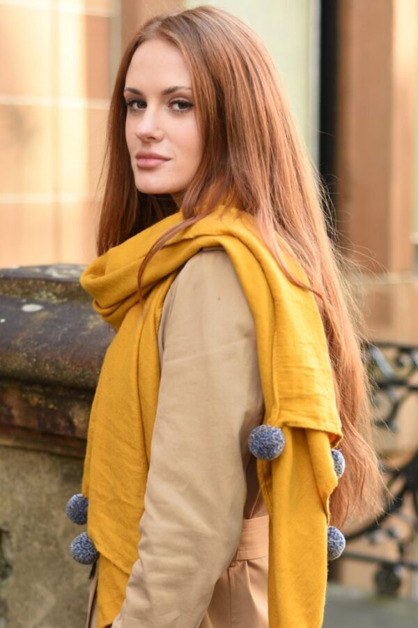 Mustard Blanket Scarf with Large Grey Pom Poms in use